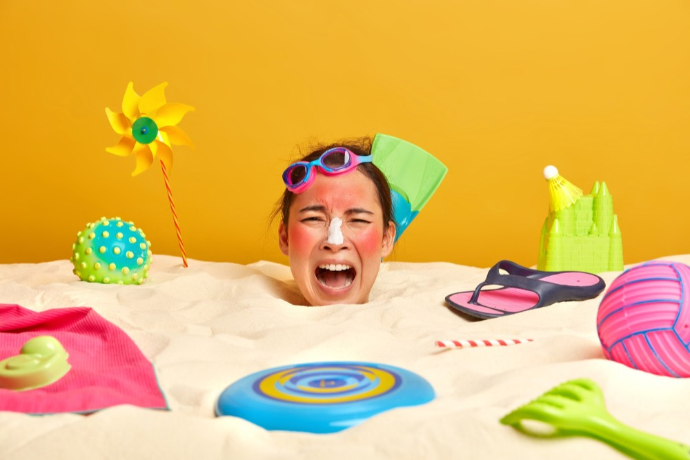 young-woman-head-with-sunscreen-cream-face-surrounded-by-beach-accessories Солнечные ожоги: первая помощь